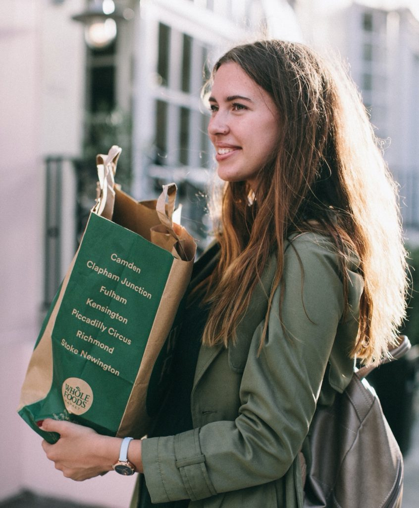 Woman holding grocery bag from Whole Foods
