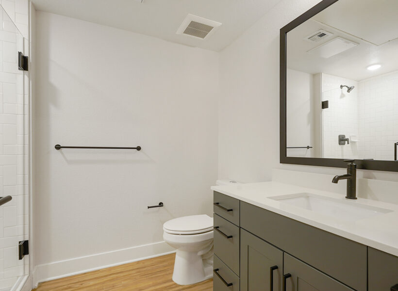 bathroom shot with gray cabinets and wood floors and white walls