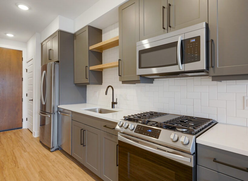 Galley kitchen with dark gray cabients and wood floors