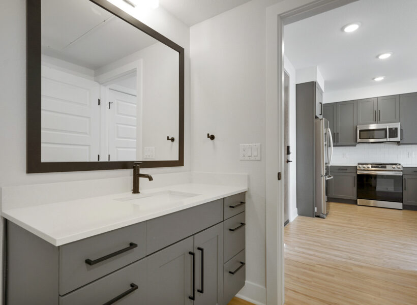 bathroom and kitchen shot with gray cabinets and wood floors