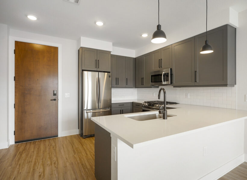 kitchen shot with dark gray cabinets and wood floors with the entry door