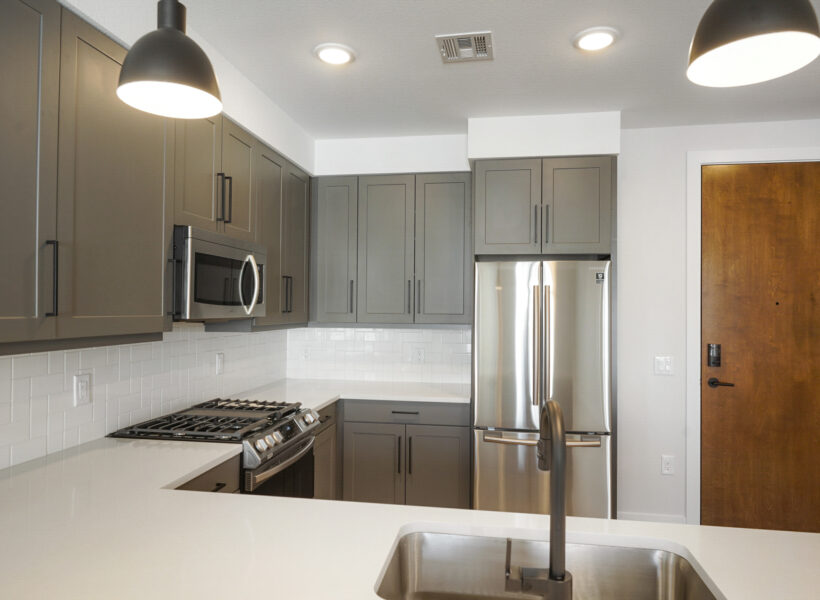 kitchen shot with gray cabinets and white walls and view of door