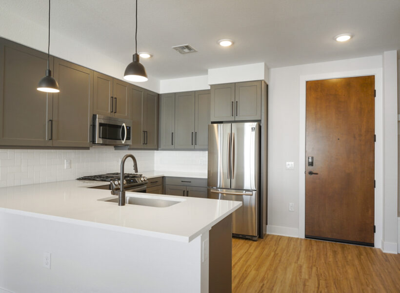 kitchen shot with gray cabinets and entry door
